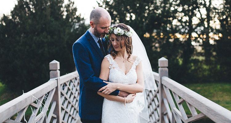 married couple on the bridge at island hall Godmanchester photo taken by island hall wedding photographer