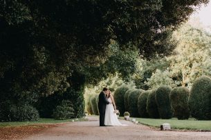 married couple walk down Wadenhoe House