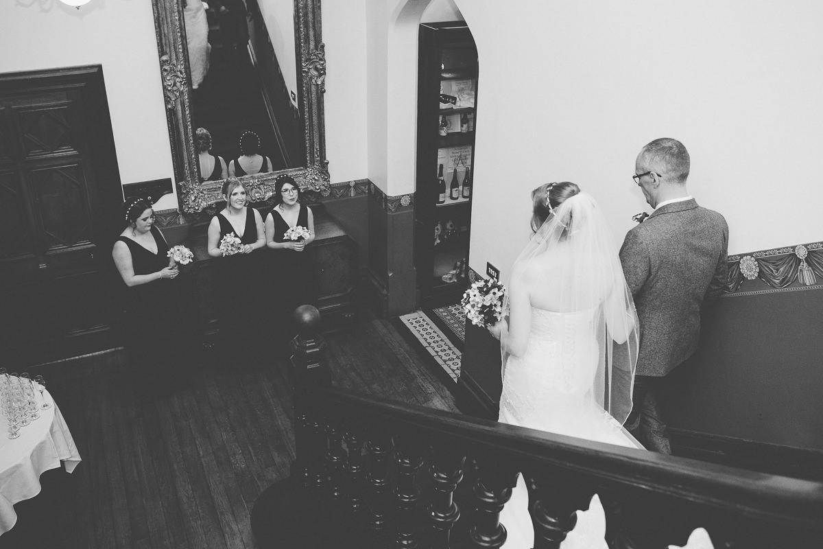 bride and father walking downstairs at Wroxall Abbey