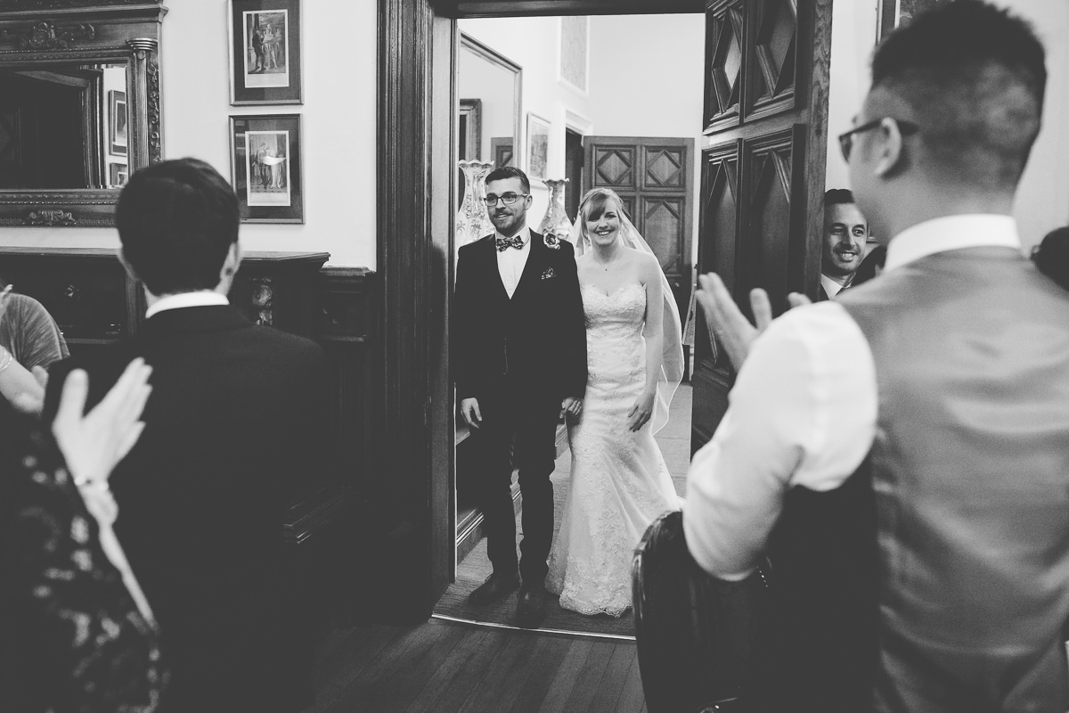 bride and groom enter the room for wedding breakfast at Wroxall Abbey