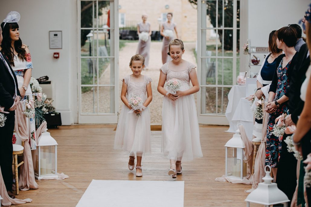 young bridesmaids walk down the aisle
