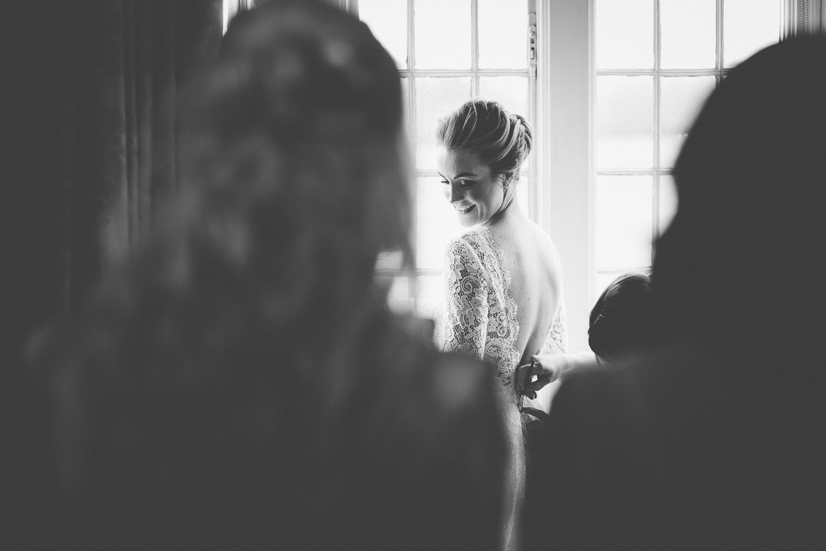 bride is putting her wedding dress on