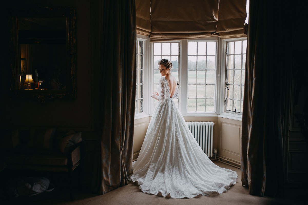 bride in a wedding dress posing at Rushton Hall