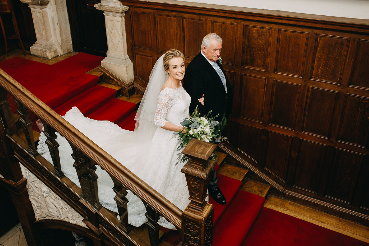 bride and father walking down the staircase at Rushton Hall