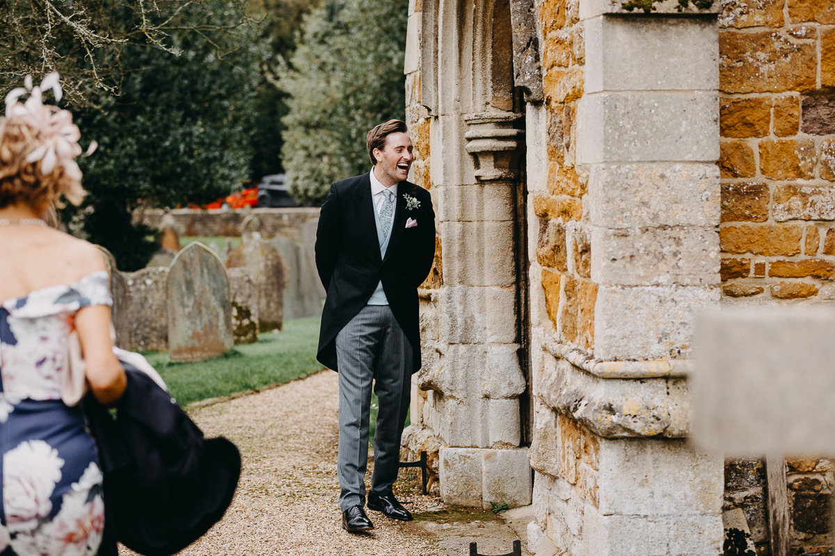 groom waiting at her bride outside of the All Saints church Rushton