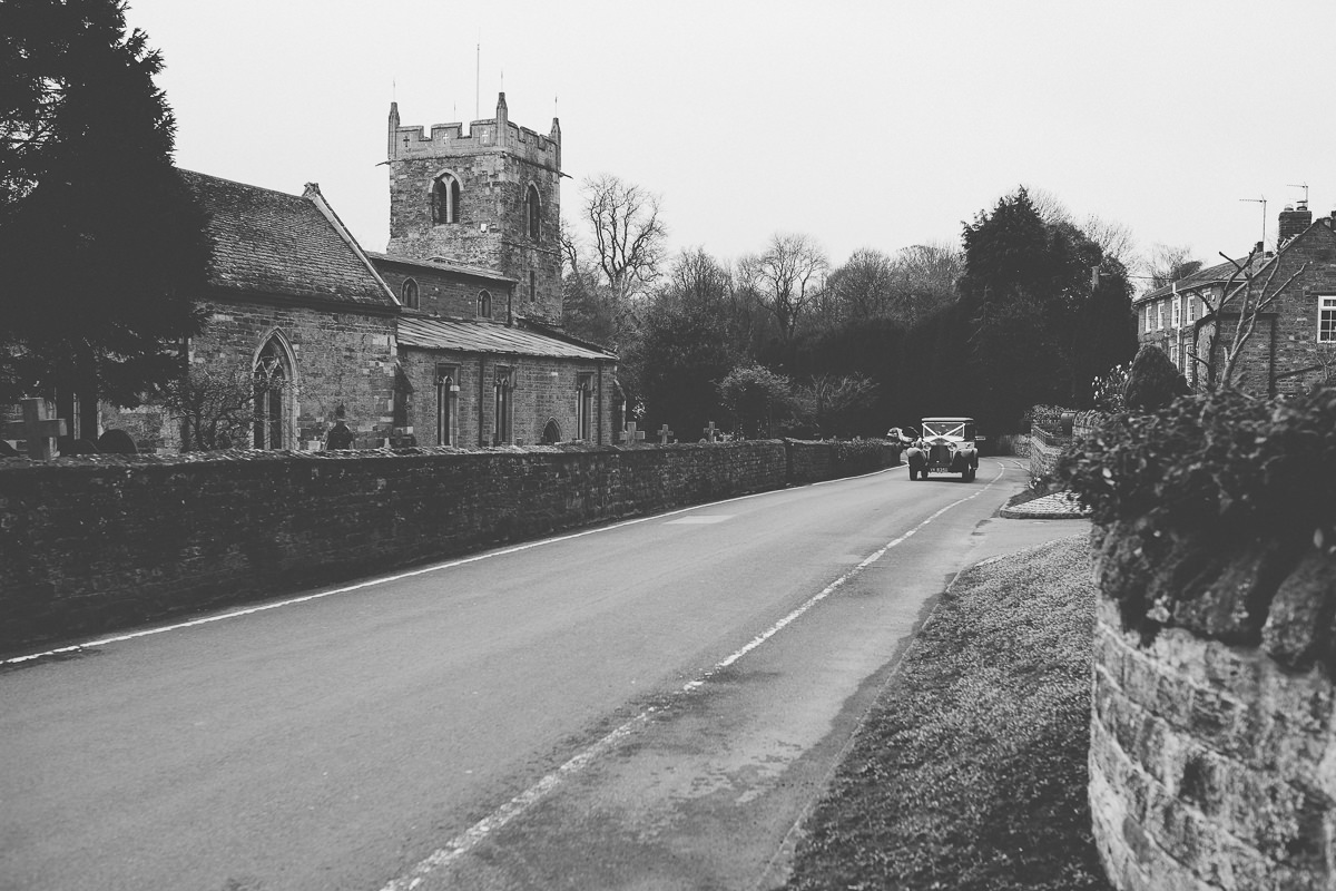 wedding car arriving at All Saints church Rushton