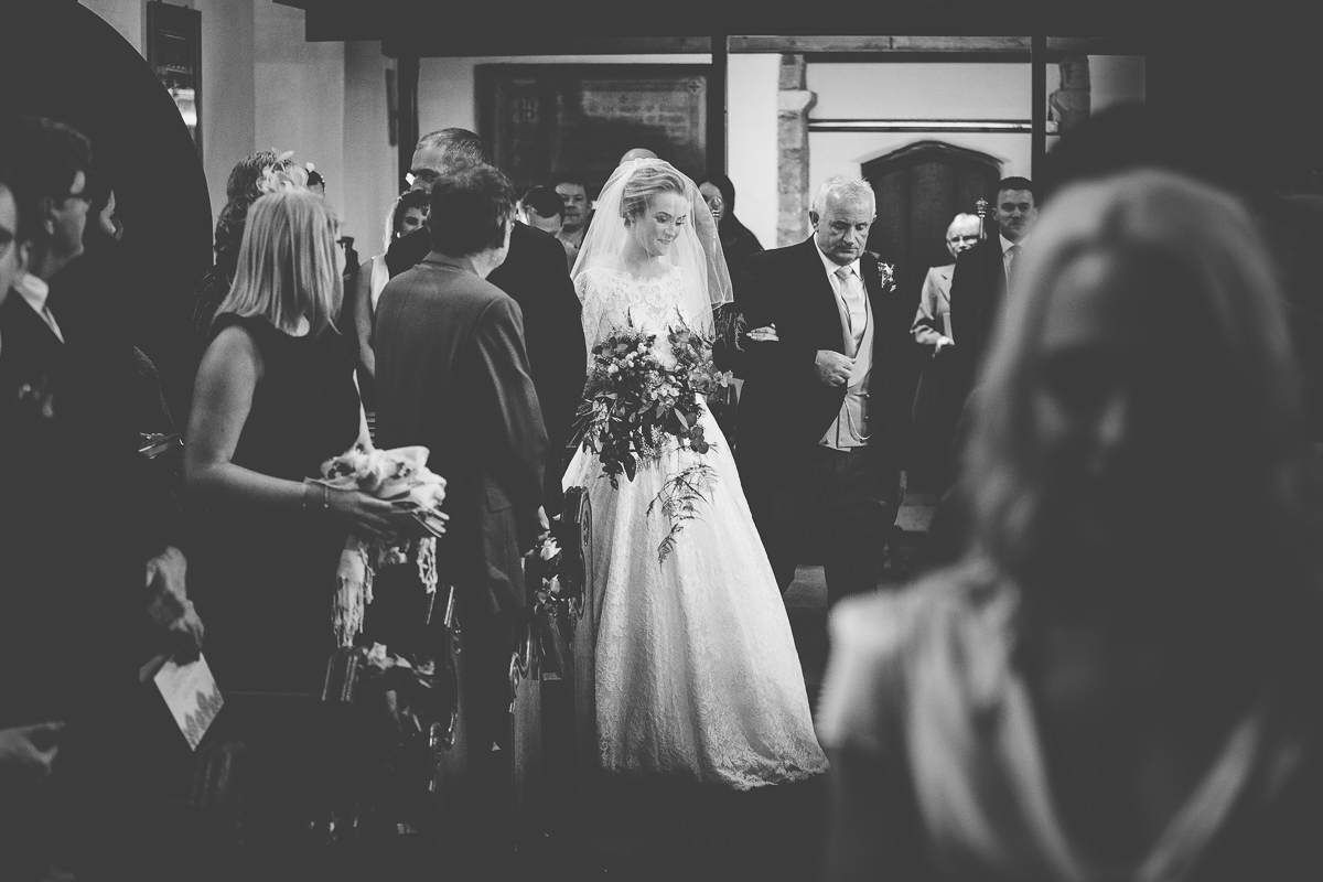 bride walking down the aisle in All Saints Church wedding at Rushton Hall