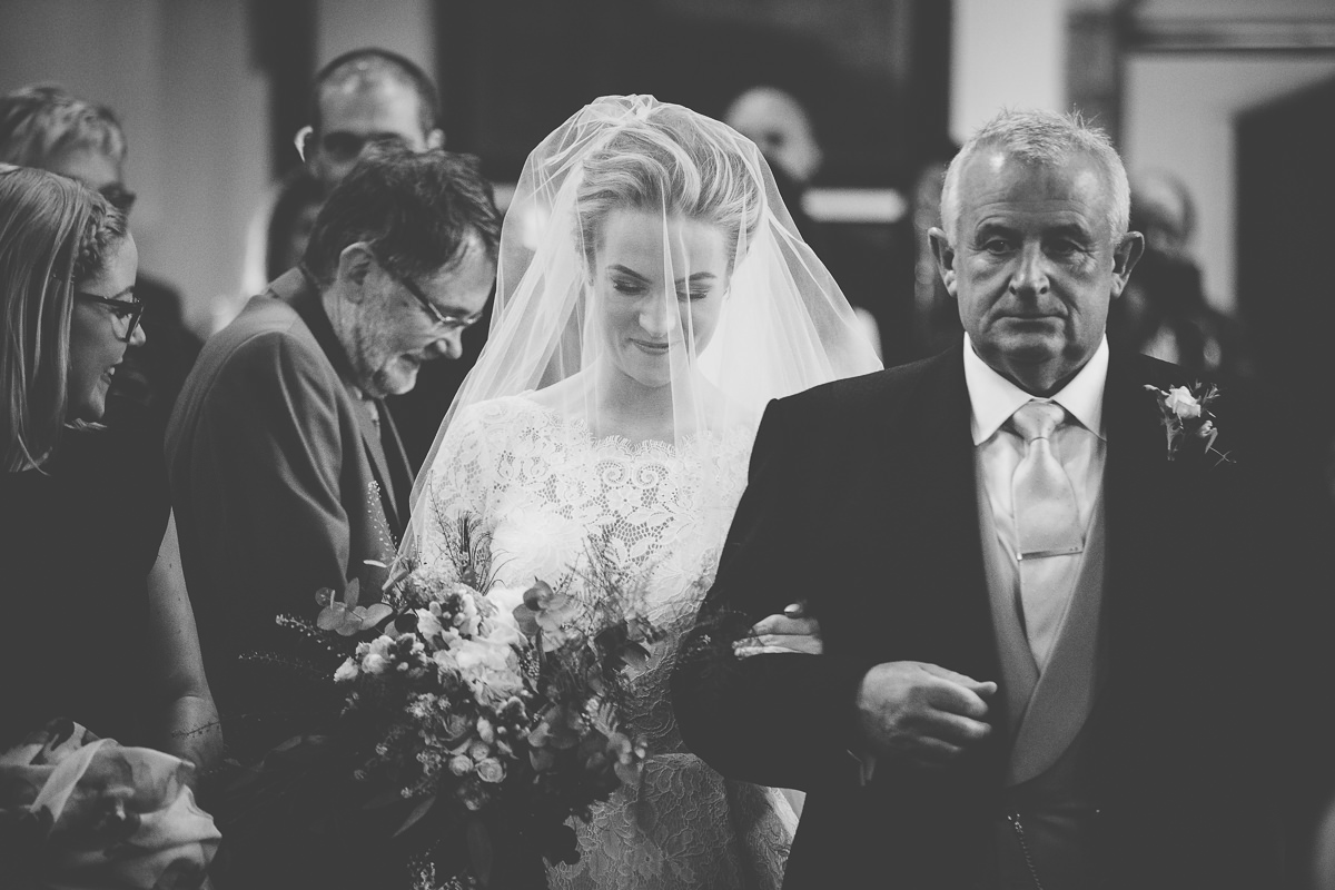 shy bride walking in to the church Rushton Hall