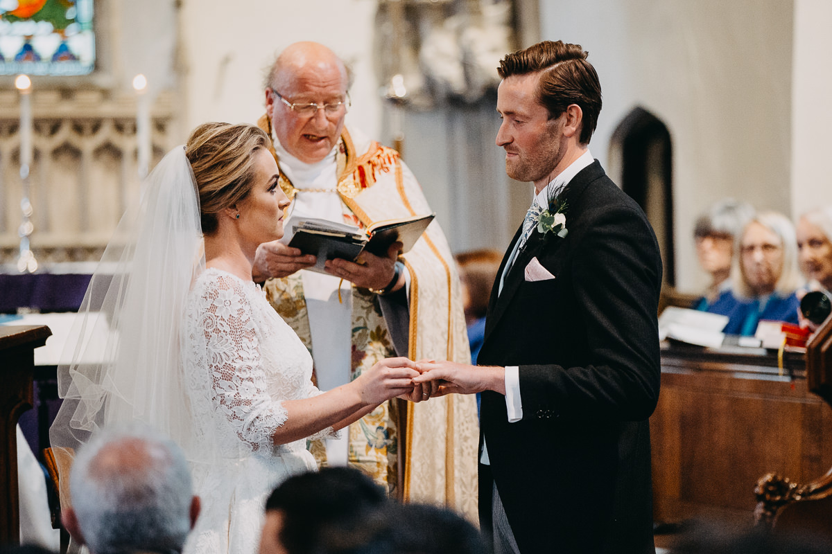 bride put ring on groom finger all saints church