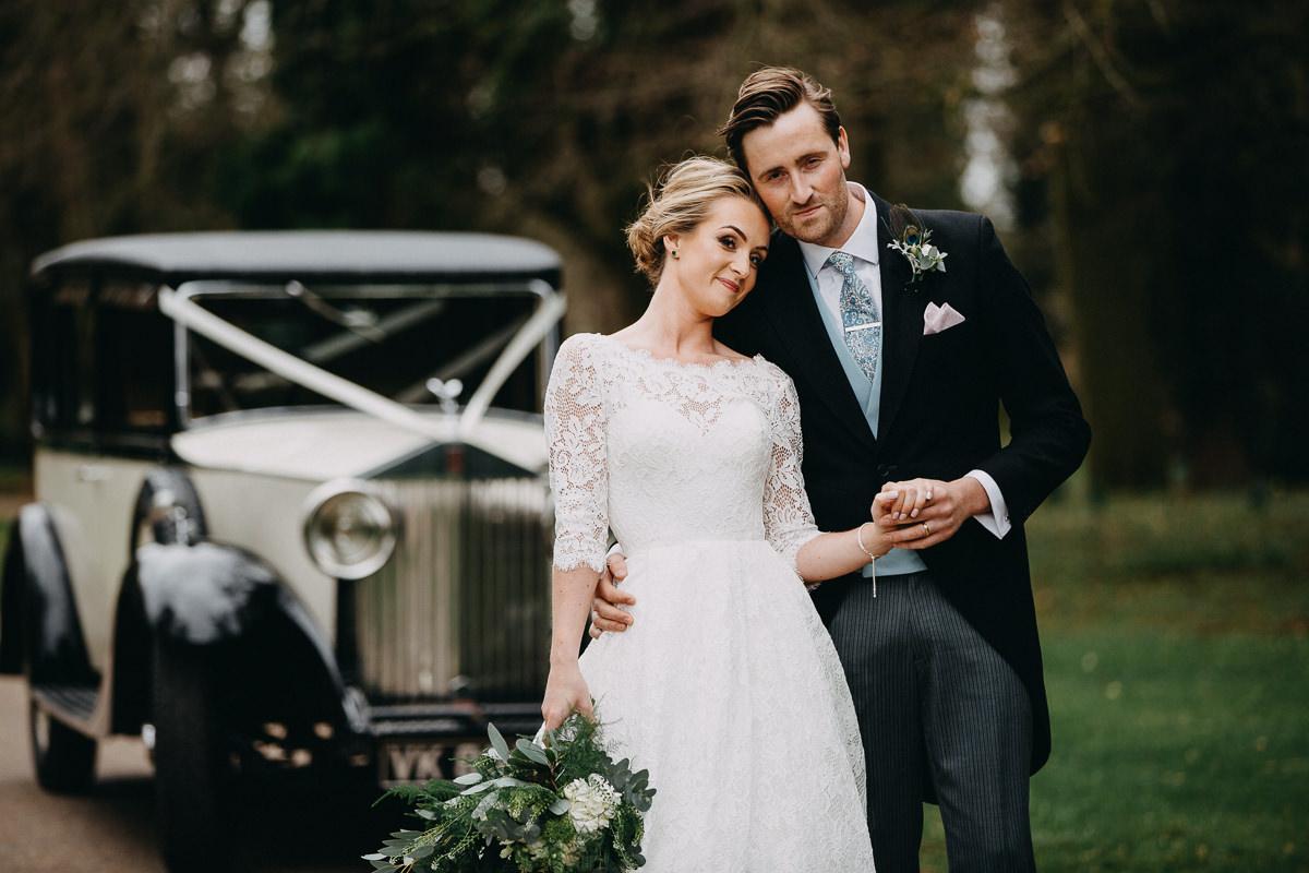bride and groom posing outside Rushton Hall