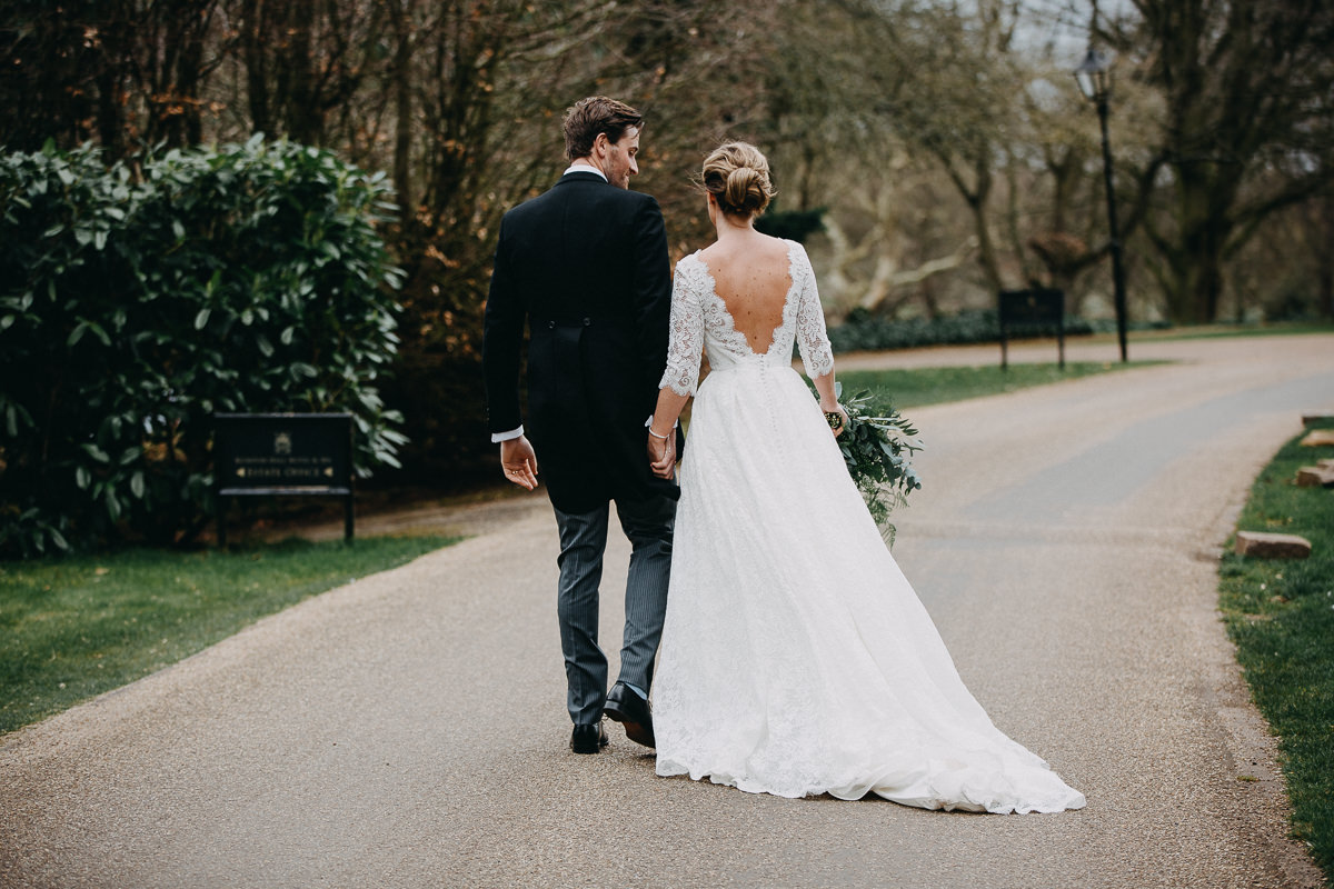 married couple walk to Rushton Hall