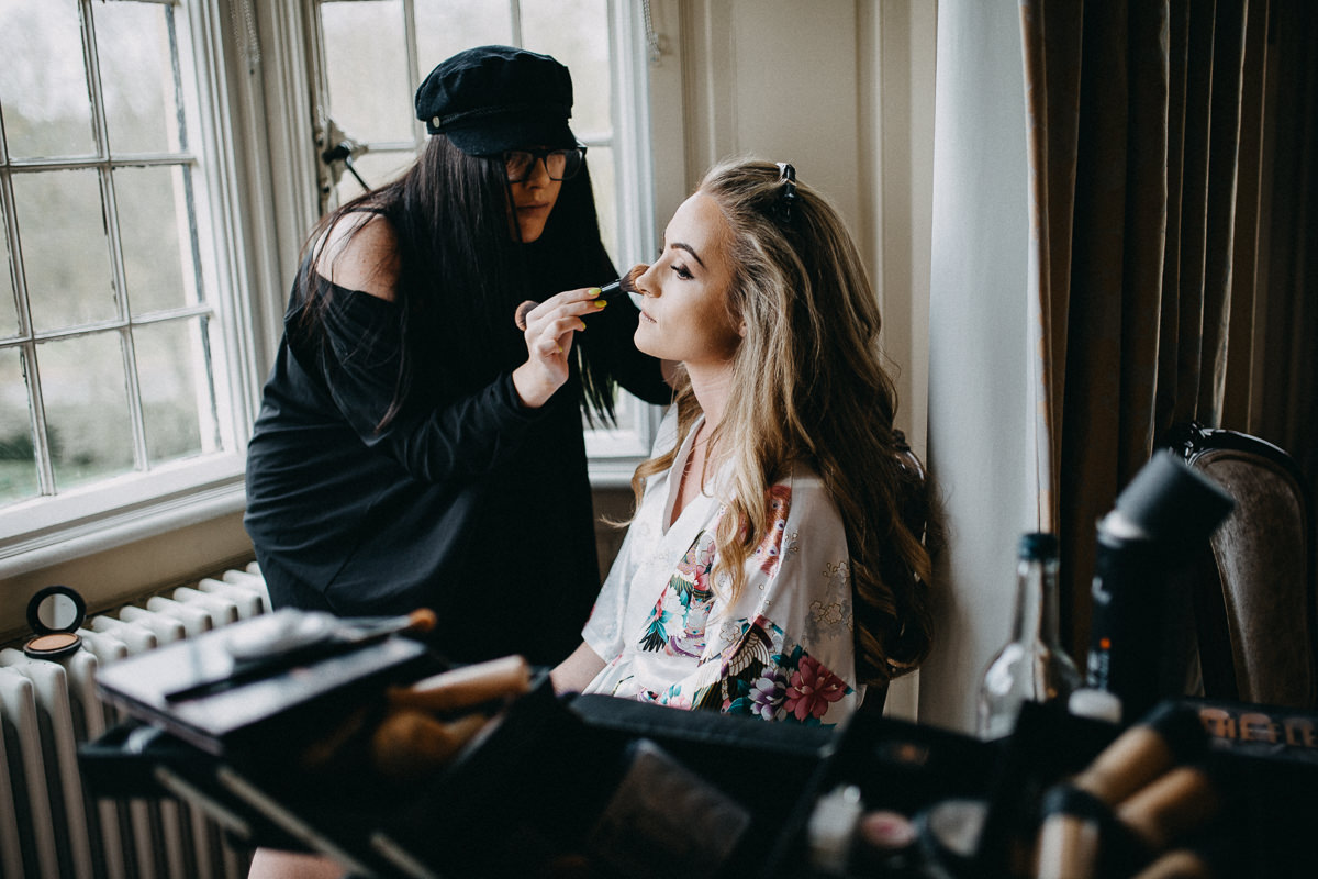 a bride having her make up done at Rushton Hall